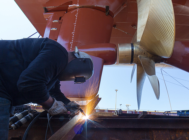 NASSCO welder makes final preparations for Lurline's launch with the propeller in the background.
