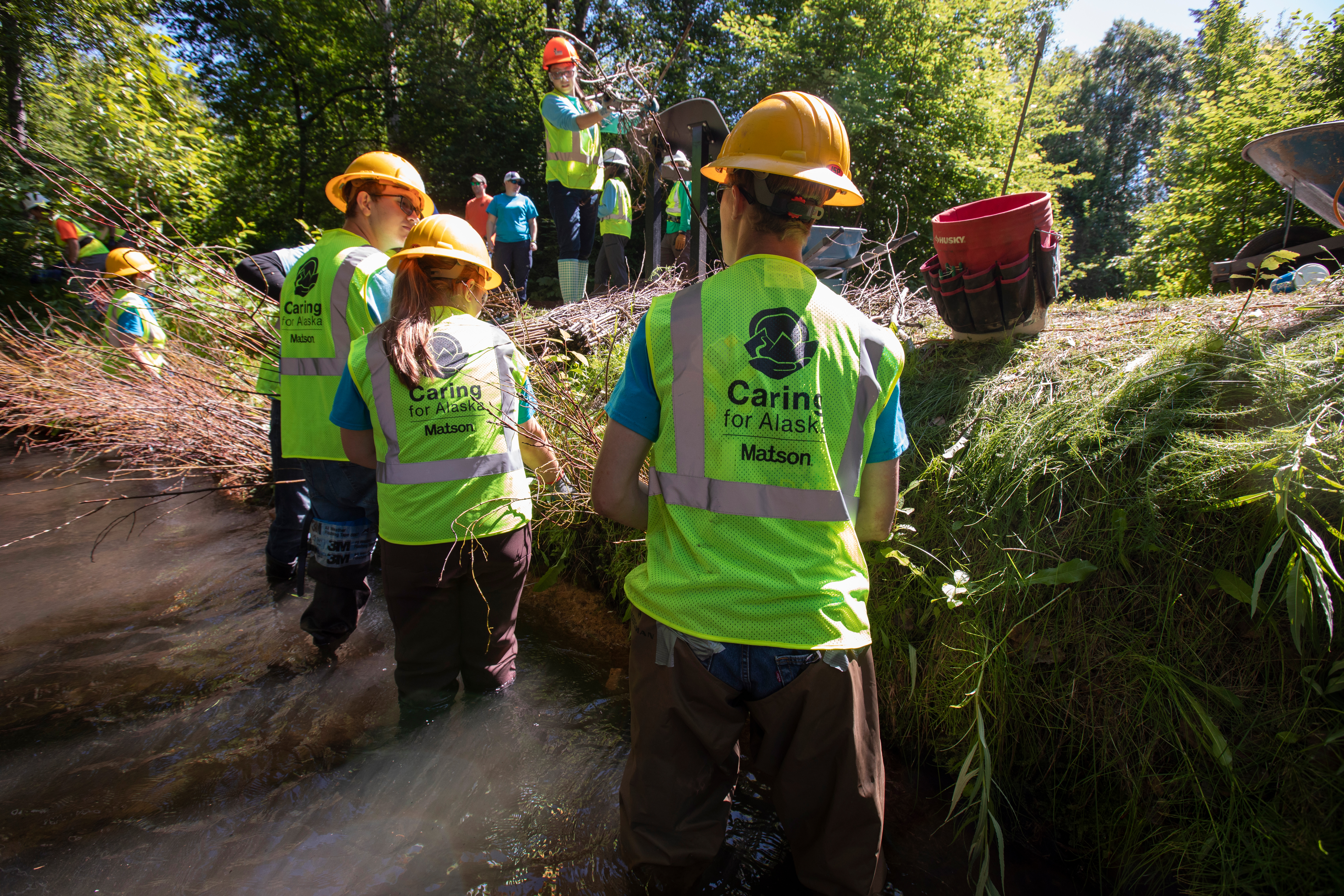 Youth Employment in Parks participants wear green safety vests and yellow hard hats while standing in Chester Creek to remove invasive species and conduct habitat restoration.